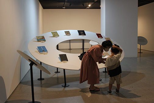 """A mother recommending a book to her child (left) and exhibited books of """"Our Stories"""" (right)"""